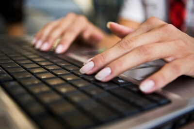 woman typing on keyboard - Typing slowly may enhance your writing skills:study